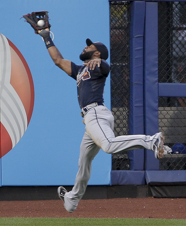 Photo - Atlanta Braves right fielder Jason Heyward (22) leaps to catch a ball hit deep by New York Mets' Eric Young Jr. in the second inning of a baseball game, Tuesday, July 8, 2014, in New York. (AP Photo/Julie Jacobson)