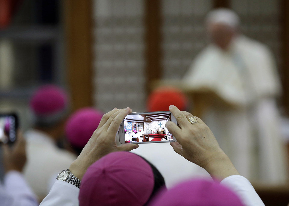 Photo - A Bishop takes a picture with a smartphone during a meeting with Pope Francis at the Shrine of Haemi, in South Korea, Sunday, Aug. 17, 2014. (AP Photo/Gregorio Borgia)