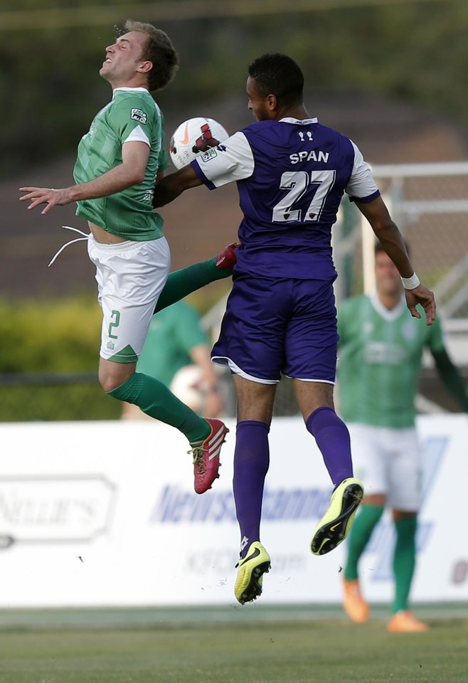 Photo - Oklahoma City's Kyle Miller and Orlando City's Brian Span jump for a loose ball during the OKC Energy FC soccer game against Orlando City SC at Pribil Stadium in Oklahoma City, Saturday, April 26, 2014. Photo by Sarah Phipps, The Oklahoman