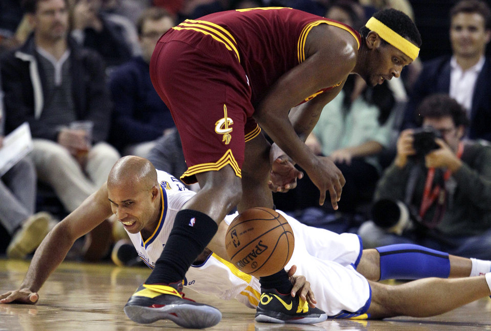 Golden State Warriors forward Richard Jefferson, bottom, reaches for the ball under Cleveland Cavaliers forward C.J. Miles during the first quarter of an NBA basketball game in Oakland, Calif., Wednesday, Nov. 7, 2012. (AP Photo/Jeff Chiu)