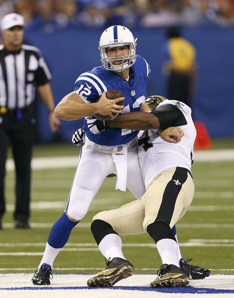 Photo - Indianapolis Colts quarterback Andrew Luck, left, is hit by New Orleans Saints defensive end Cameron Jordan during the first half of an NFL preseason football game in Indianapolis, Saturday, Aug. 23, 2014. (AP Photo/Sam Riche)