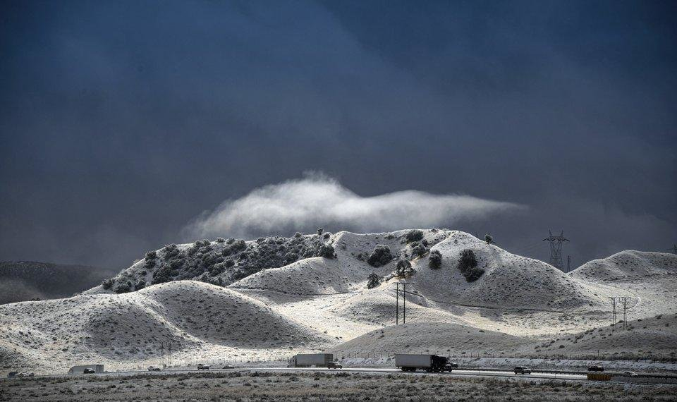 Photo - A dramatic sky opens up between snow squalls along the Interstate 5 freeway near Gorman, Calif., Wednesday, Nov. 27, 2019. Plows were running and CHP was escorting traffic in an attempt to keep the freeway open as long as possible. [David Crane/The Orange County Register via AP]