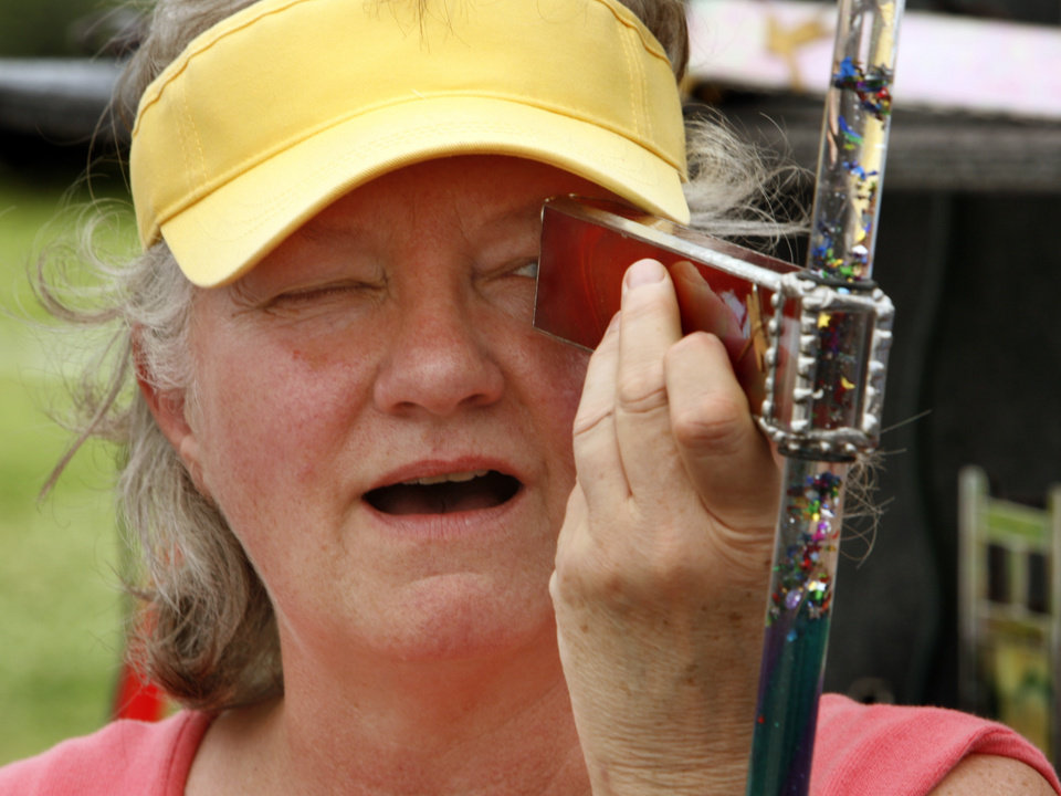 Photo - Tami James of Norman looks though a kaleidoscope made by Rogers, Arkansas artist Hank Barnes during May Fair Arts Festival in Norman, Okla. on Friday, May 1, 2009.   Photo by Steve Sisney, The Oklahoman