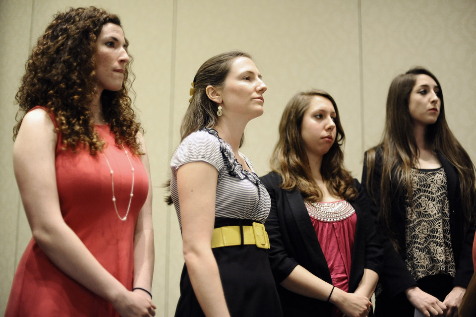 Photo - University of Connecticut students Rosemary Richi, left, Kylie Angell, second from left, Erica Daniels, second from right, and Carolyn Luby, right, listen to attorney Gloria Allred speak during a news conference, Friday, July 18, 2014, in Hartford, Conn. The University of Connecticut will pay nearly $1.3 million to settle a federal lawsuit filed by five women who claimed the school responded to their sexual assault complaints with indifference, the two sides announced Friday.  (AP Photo/Jessica Hill)