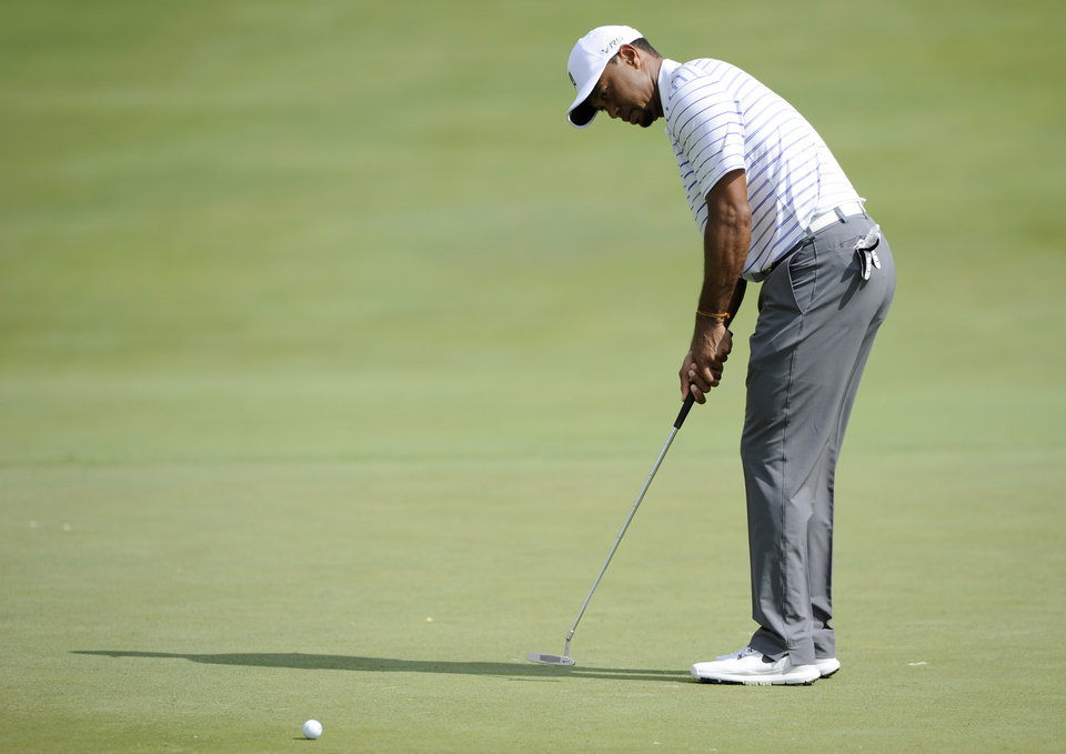Photo - Tiger Woods putts on the fifth green during the Pro-Am at the Quicken Loans National golf tournament, Wednesday, June 25, 2014, in Bethesda, Md. (AP Photo/Nick Wass)