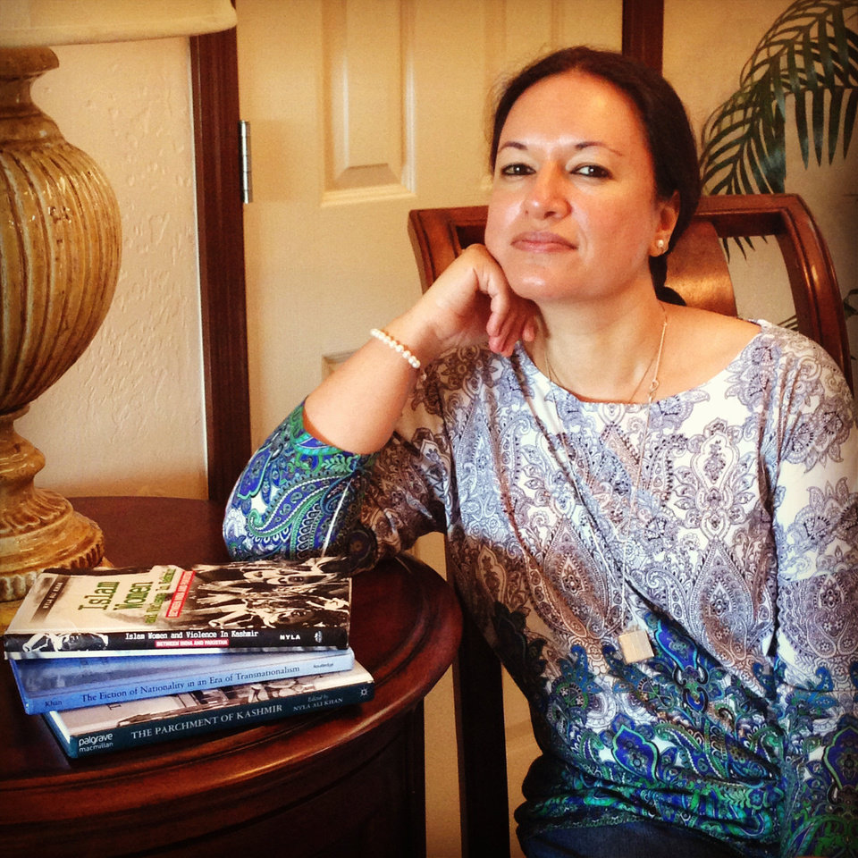 Photo - Nyla Ali Khan, a noted scholar and author on Kashmiri culture and politics, is pictured with three books she has published.  Photo by Ashley Gibson, for The Oklahoman.
