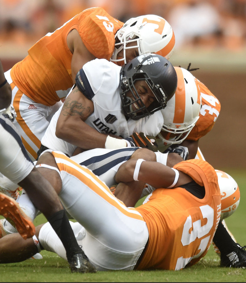 Photo - Utah State wide receiver Brandon Swindall (11) is tackled by Tennessee defensive back Devaun Swafford (13), linebacker Jalen Reeves-Maybin (34), and, defensive back Brian Randolph (37) during their NCAA college football game against Utah State at Neyland Stadium, Sunday, Aug. 31, 2014 in Knoxville, Tenn.  (AP Photo/Knoxville News Sentinel, Saul Young)
