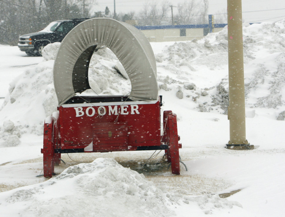 Photo - A promotional Sooner Schooner sits in front of Billy Sim's BBQ restaurant between piles of snow in a parking lot at 24th Ave NW and Main as the second round of snow in a week moved into the area on Wednesday, February 9, 2011, in Norman, Okla.   Photo by Steve Sisney, The Oklahoman