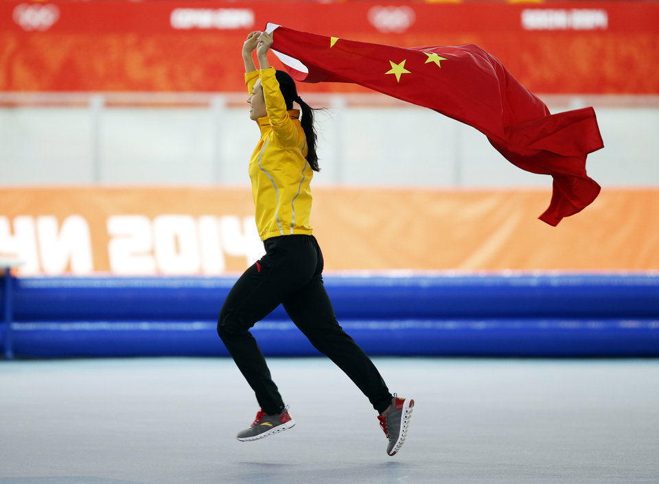 Photo - Gold medallist China's Zang Hong holds her national flag and runs in celebration after the women's 1,000-meter speedskating race at the Adler Arena Skating Center during the 2014 Winter Olympics in Sochi, Russia, Thursday, Feb. 13, 2014. (AP Photo/Pavel Golovkin, File)