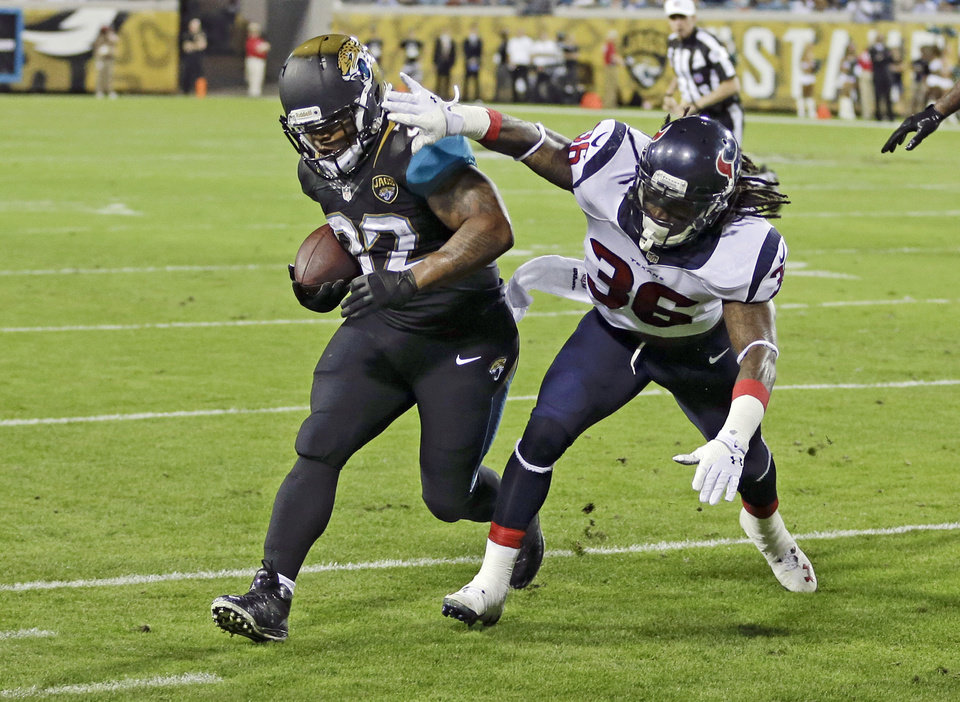 Jacksonville Jaguars running back Maurice Jones-Drew, left, gains yardage before he is run out of bounds by Houston Texans strong safety D.J. Swearinger (36) during the first half of an NFL football game in Jacksonville, Fla., Thursday, Dec. 5, 2013.(AP Photo/John Raoux)