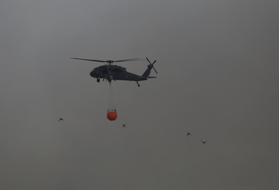 Photo - A helicopter drops water near SE 164th Street as a wildfire burns in the area in southeast Oklahoma City, Okla., Sunday, Feb. 12, 2017. Photo by Sarah Phipps, The Oklahoman