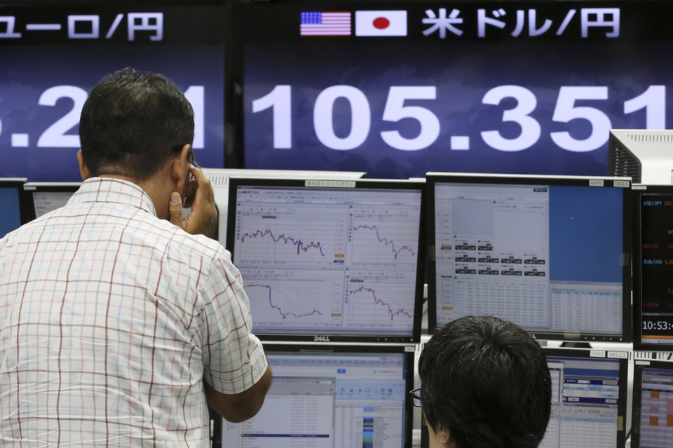 Photo - Money traders of a foreign exchange company work in front of a an electric monitor displaying the current exchange rate of Japanese yen against U.S. dollar in Tokyo, Friday, Sept. 5, 2014. The U.S. dollar rose to around 105.70 yen, the highest since October 2008, on Friday morning. (AP Photo/Koji Sasahara)