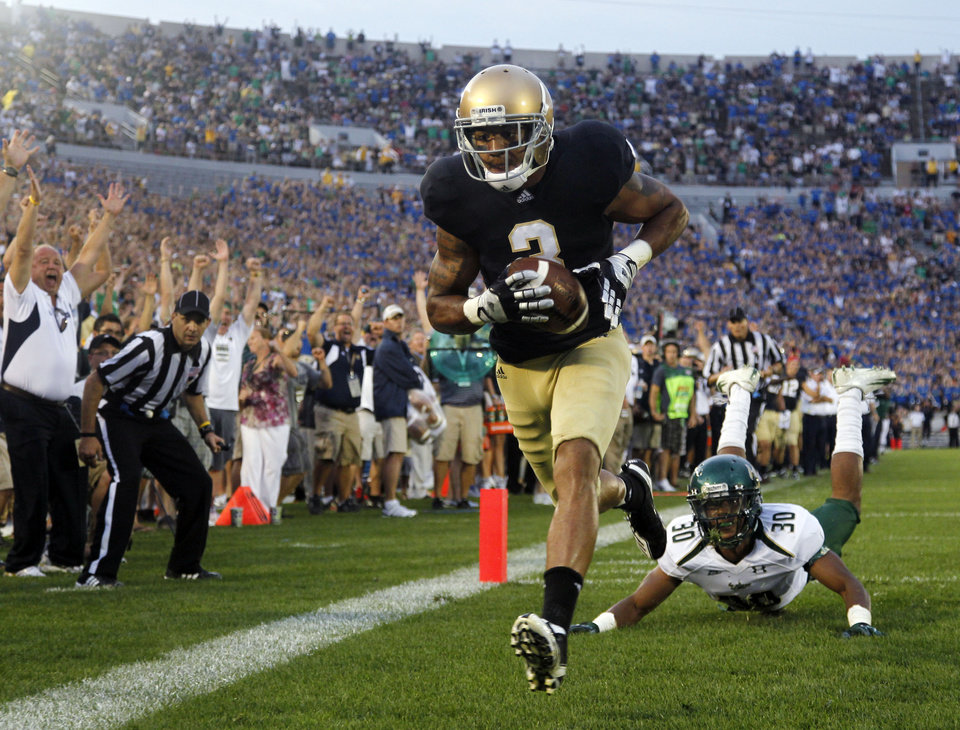 Notre Dame wide receiver Michael Floyd scores a touchdown in front of South Florida safety JaQuez Jenkins in the third quarter of an NCAA college football game in South Bend, Ind., Saturday, Sept. 3, 2011. (AP Photo/Michael Conroy)