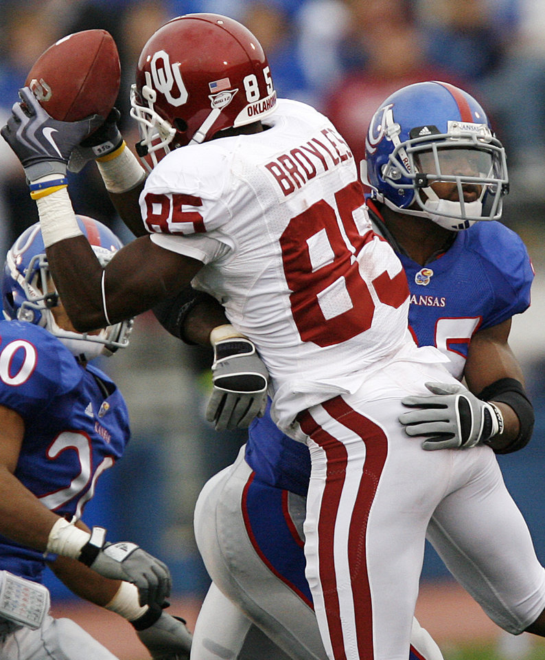 Photo - Oklahoma's Ryan Broyles (85) is hit by Kansas' Darrell Stuckey (25) as Broyles makes a reception during the second half of the college football game between the University of Oklahoma Sooners (OU) and the University of Kansas Jayhawks (KU) on Saturday, Oct. 24, 2009, in Lawrence, Kan. Oklahoma won the game 35-13. Photo by Chris Landsberger, The Oklahoman