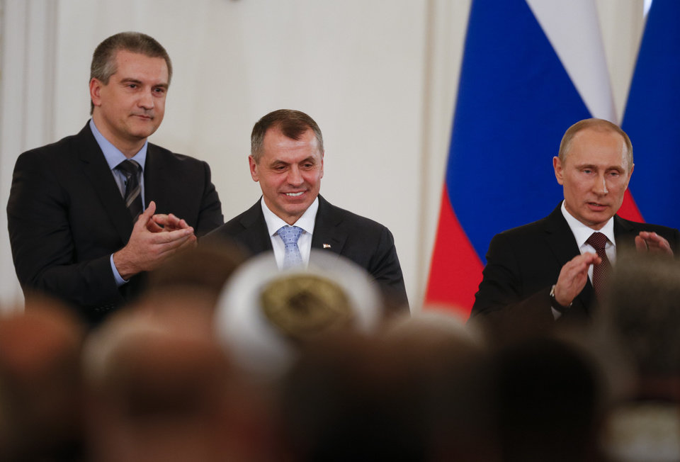 Photo - Russian President Vladimir Putin, right, Speaker of Crimean legislature Vladimir Konstantinov, center, and Crimean Premier Sergei Aksyonov stand after signing a treaty to incorporate Crimea into Russia in the Kremlin in Moscow,  Tuesday, March 18, 2014. President Vladimir Putin on Tuesday signed a treaty to incorporate Crimea into Russia, describing the move as the restoration of historic injustice and a necessary response to what he called the Western encroachment on Russia's vital interests.  (AP Photo/Alexander Zemlianichenko)