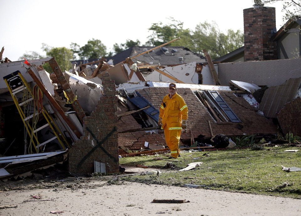 Photo - An official looks at damage, Sunday, April 15, 2012.  A tornado struck Woodward early Sunday morning. Photo by Sarah Phipps, The Oklahoman.