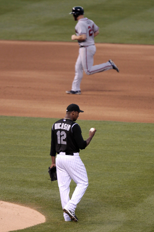 Photo - Colorado Rockies starting pitcher Juan Nicasio (12) looks at the ball as Atlanta Braves catcher Evan Gattis rounds the base after hitting a home run in the fourth inning of a baseball game in Denver on Tuesday, June 10, 2014. (AP Photo/Joe Mahoney)