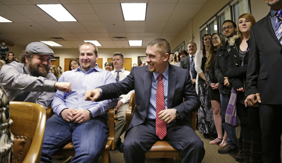 Photo - Sean Green, seated right, is congratulated by Sean Fitzgerald, left, as Scott O'neil looks on before Green is issued his new Washington state legal marijuana license Wednesday, March 5, 2014, in Olympia, Wash. Green, a medical marijuana dispensary operator from Spokane, was issued the producer-processor license under the state's recreational pot law at the Liquor Control Board meeting. (AP Photo/Elaine Thompson)