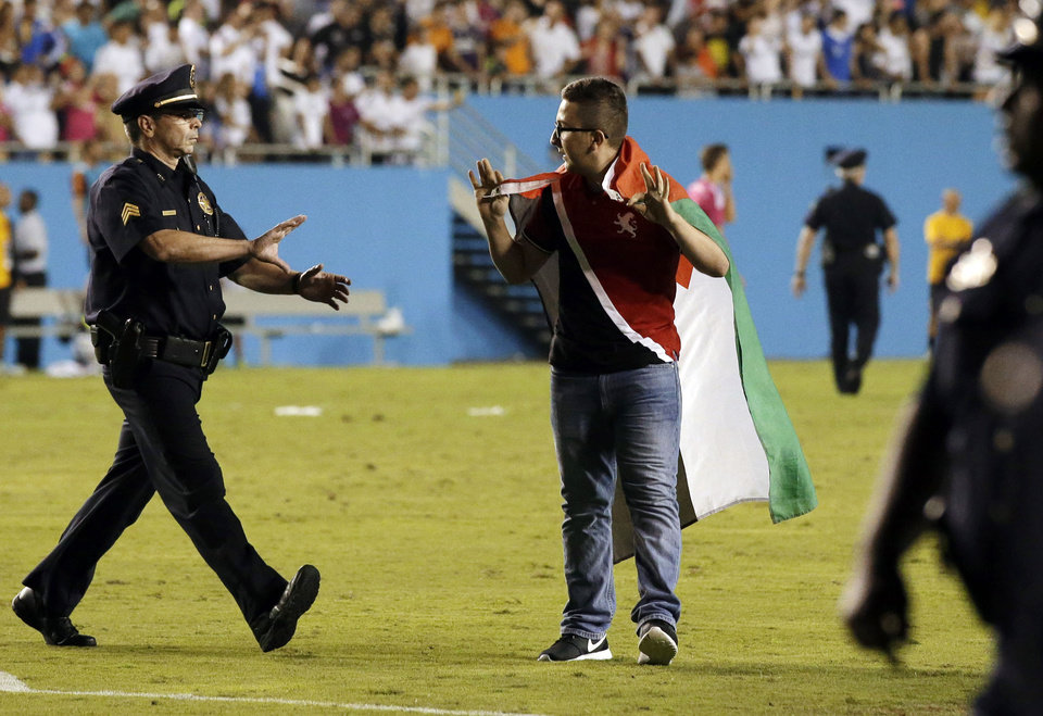 Photo - Police officers approach a fan that ran onto the field with several others during the second half of a Guinness International Champions Cup soccer tournament match between Roma and Real Madrid, Tuesday, July 29, 2014, in Dallas. Roma won 1-0. (AP Photo/Tony Gutierrez)