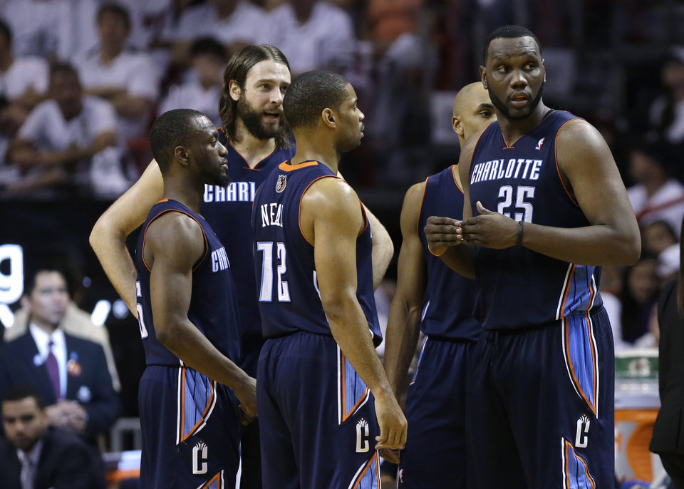 Photo - Charlotte Bobcats' Al Jefferson (25) talks with Kemba Walker, left, Josh McRoberts, second from left, and Gary Neal (12) during the second half in Game 1 of an opening-round NBA basketball playoff series against the Miami Heat, Sunday, April 20, 2014, in Miami. The Heat defeated the Bobcats 99-88. (AP Photo/Lynne Sladky)