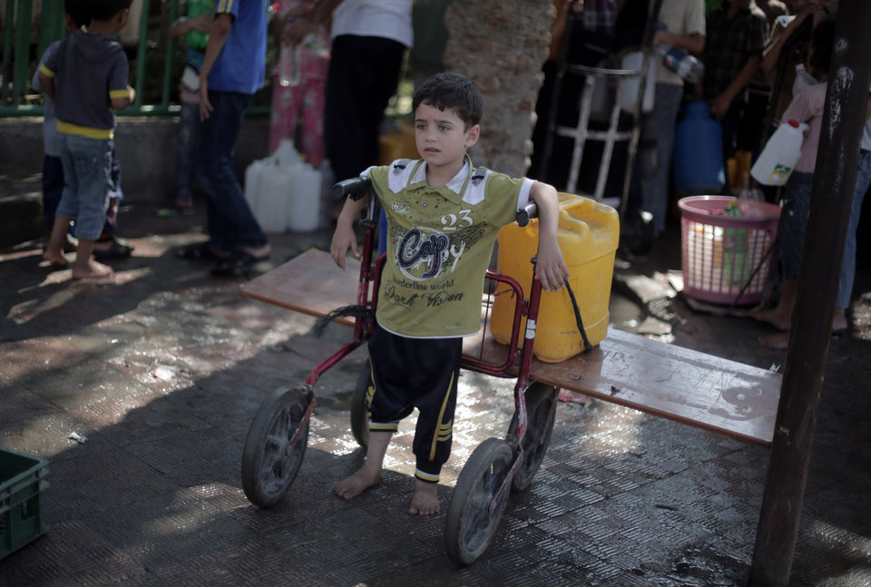 Photo - A Palestinian boy waits to fill a plastic container with drinking water at a public tap in the town of Jabaliya in the northern Gaza Strip, Sunday, July 27, 2014. Israel resumed its Gaza offensive on Sunday, calling off a unilateral extension of a humanitarian cease-fire after Palestinian militants fired several rockets at southern Israel.(AP Photo/Khalil Hamra)