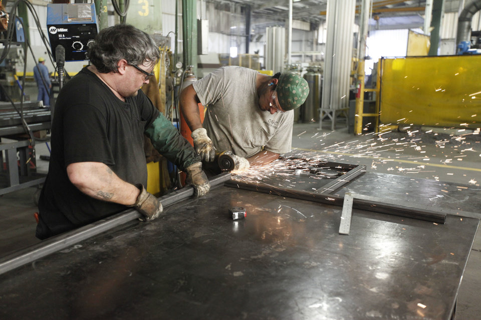 Photo - Machinists assemble a metal framework at the Chickasaw Nation Industries in Marietta, OK, Monday, July 22, 2013,  Photo by Paul Hellstern, The Oklahoman