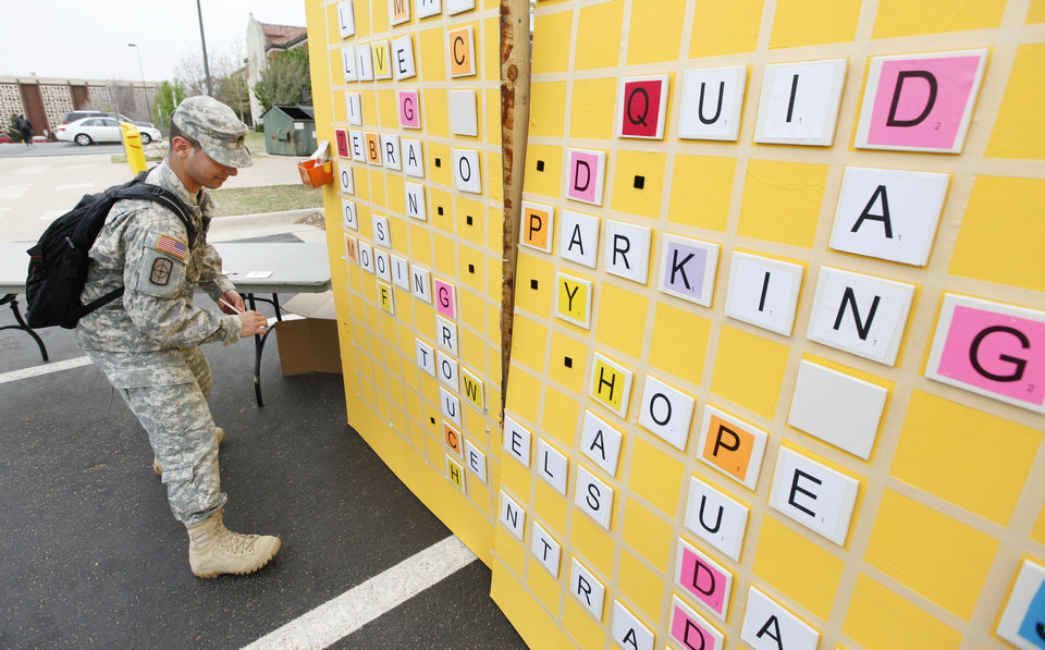 Photo - ROTC cadet George Delisle plays a giant game of Scrabble on Tuesday during UCO Earth Day Week's Park-ing Day at the University of Central Oklahoma in Edmond. Photos By Paul Hellstern, The Oklahoman