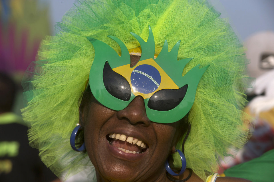 Photo - A Brazil soccer fan in costume cheers before the start of a live broadcast of her team's World Cup match with Mexico inside the FIFA Fan Fest area on Copacabana beach, in Rio de Janeiro, Brazil, Tuesday, June 17, 2014. (AP Photo/Silvia Izquierdo)