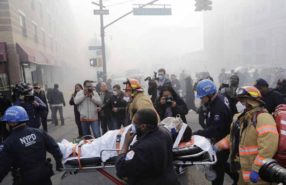 Rescue workers remove an injured person on a stretcher after a possible explosion and building collapse in the East Harlem neighborhood of New York, Wednesday, March 12, 2014 (AP Photo/Mark Lennihan)