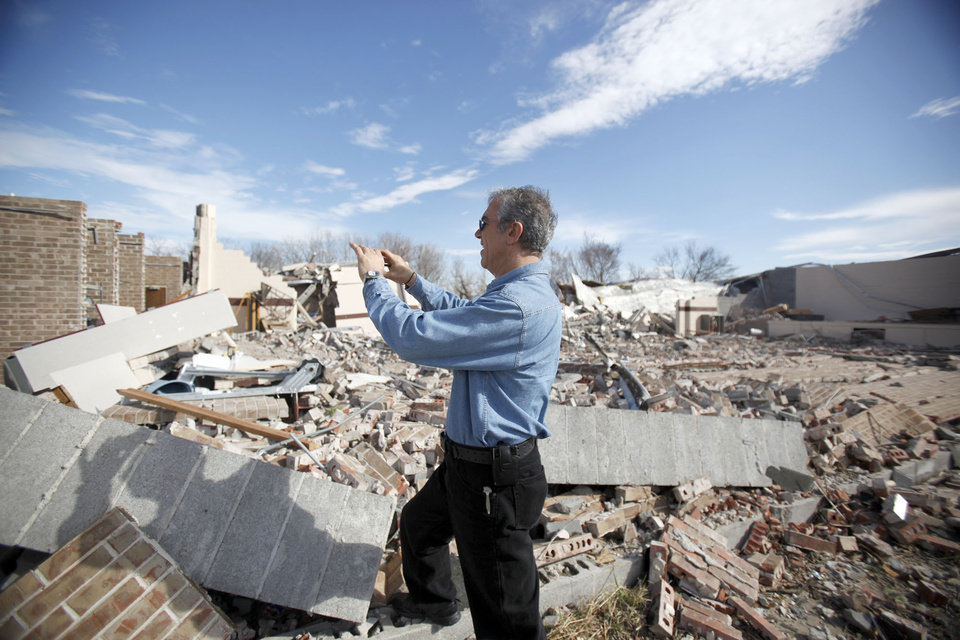 Photo - TORNADO DAMAGE: Allen Zahrai, with the National Severe Storms Laboratory, walks past debris at the Ardmore Adventist Academy near the Majestic Hills neighborhood north of Ardmore, Thursday, Feb. 12, 2009, PHOTO BY SARAH PHIPPS, THE OKLAHOMAN ORG XMIT: KOD