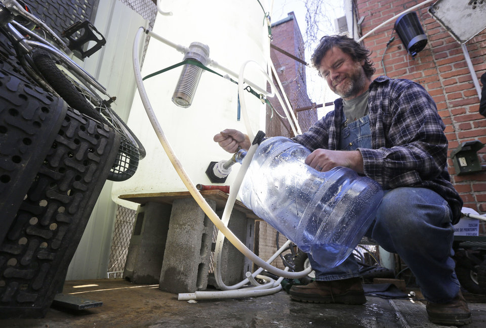 Photo - Jonathan Steele, owner of Bluegrass Kitchen, fills a jug with cleaning water in the back of his restaurant in Charleston, W.Va., Tuesday, Jan. 14, 2014. Steele installed a large tank in the back of his restaurant and was able to open his restaurant using bottled water on Sunday.  .  (AP Photo/Steve Helber)