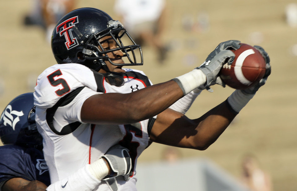 Photo - Texas Tech University wide receiver Michael Crabtree (5) catches a 25-yard touchdown pass as Rice University's Brandon King, left, defends during the fourth quarter of a college football game Saturday, Sept. 15, 2007, in Houston. (AP Photo/David J. Phillip) ORG XMIT: TXDP107