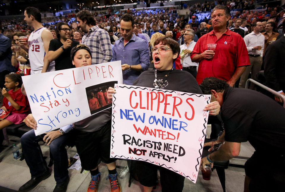 Photo - Fans hold up signs in support of the Los Angeles Clippers before Game 5 of an opening-round NBA basketball playoff series between the Clippers and the Golden State Warriors on Tuesday, April 29, 2014, in Los Angeles. NBA Commissioner Adam Silver announced Tuesday that Clippers owner Donald Sterling has been banned for life by the league. (AP Photo/Ringo H.W. Chiu)