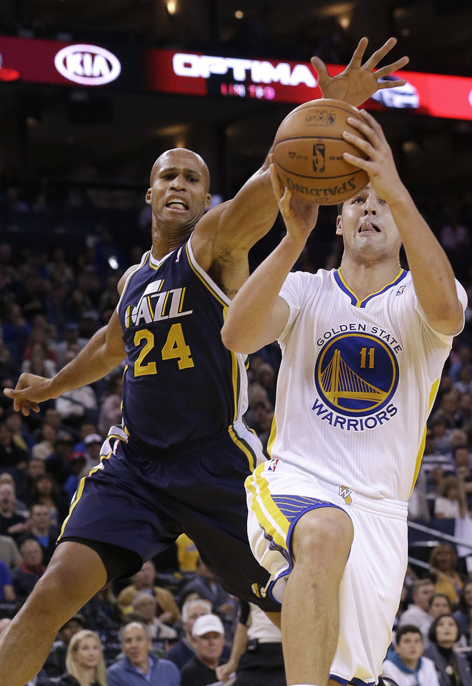 Photo - Golden State Warriors shooting guard Klay Thompson (11) shoots against Utah Jazz small forward Richard Jefferson (24) during the first quarter of an NBA basketball game in Oakland, Calif., Saturday, Nov. 16, 2013. (AP Photo/Jeff Chiu)