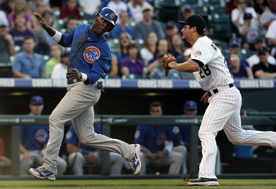Chicago Cubs' Junior Lake, left, runs from Colorado Rockies third baseman Nolan Arenado before being tagged out during a rundown between third base and home plate in the second inning of a baseball game in Denver, Friday, July 19, 2013. (AP Photo/Joe Mahoney)
