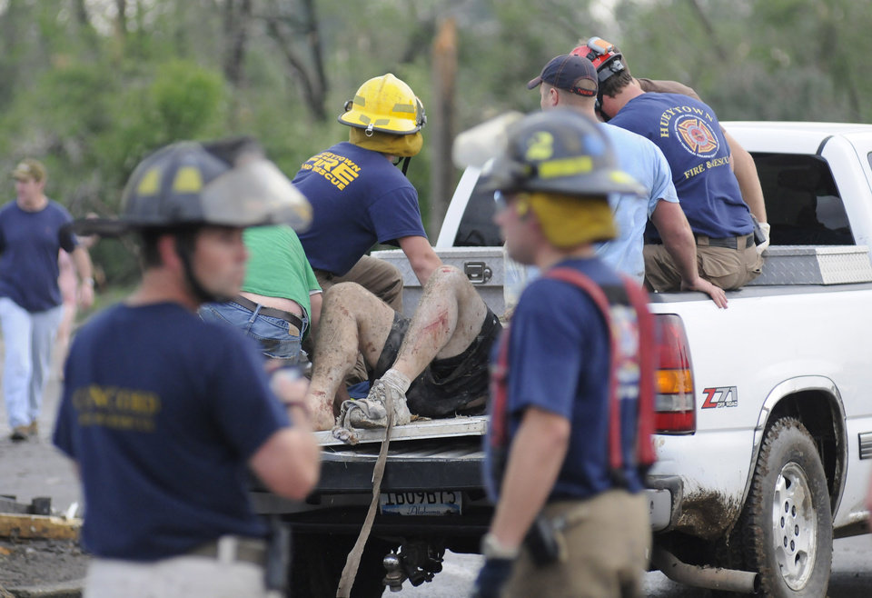 Photo - Rescue workers tend to an injured person after what appeared to be a tornado ripped through parts of Concord, Ala., Wednesday, April 27, 2011. A wave of tornado-spawning storms strafed the South on Wednesday, splintering buildings across hard-hit Alabama and killing 72 people in four states. At least 58 people died in Alabama alone. (AP Photo/Birmingham News, Jeff Roberts)