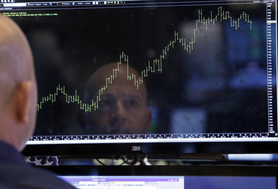 Photo - Specialist Jay Woods is reflected in a screen at his post on the floor of the New York Stock Exchange Thursday, Oct. 10, 2013. Wall Street roared in approval Thursday after Washington appeared to break an impasse that threatened to push the country into default.  (AP Photo/Richard Drew)