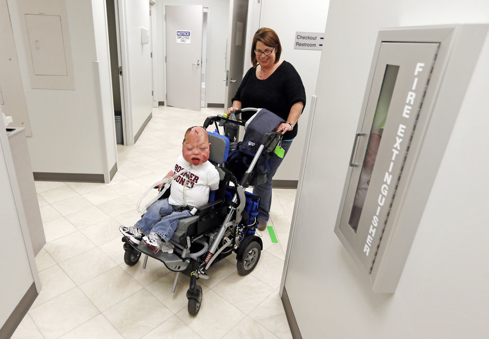 Photo - Denise Burns pushes her son, Fletcher Burns, 8, to a therapy appointment at the Children's Center in Bethany. Photo by Nate Billings, The Oklahoman  NATE BILLINGS - NATE BILLINGS