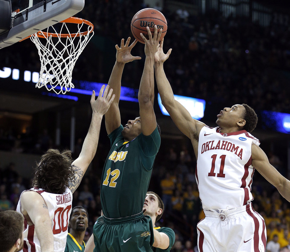 Photo - North Dakota State's Lawrence Alexander (12) grabs a rebound from Oklahoma's Ryan Spangler (00) and Isaiah Cousins (11) during the NCAA men's basketball tournament game between the University of Oklahoma and North Dakota State at the Spokane Arena in Spokane, Wash., Thursday, March 20, 2014. Oklahoma home lost 80-75. Photo by Sarah Phipps, The Oklahoman