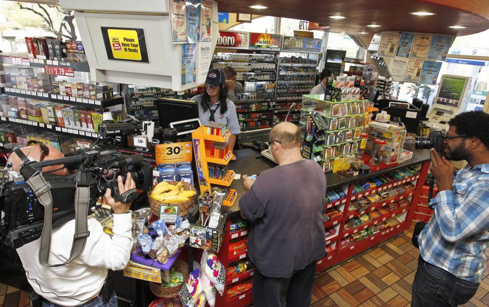 In this Nov. 29, 2012 file photo, members of the media document store cashier Tanice Stefanich helping a customer at a 4 Sons Food Store where one of the winning tickets in the $579.9 million Powerball jackpot was purchased in Fountain Hills, Ariz.  When two winning tickets for a record Powerball jackpot were claimed last month, the world focused on the winners. One, from Missouri, showed up at the newsconference, while the other, in Arizona, chose to remain anonymous. Releasing information on the lottery winners reflects a broader debate playing out in state Legislatures and lottery offices nationwide: Should the winners� names be made public?(AP Photo/Ross D. Franklin, file)