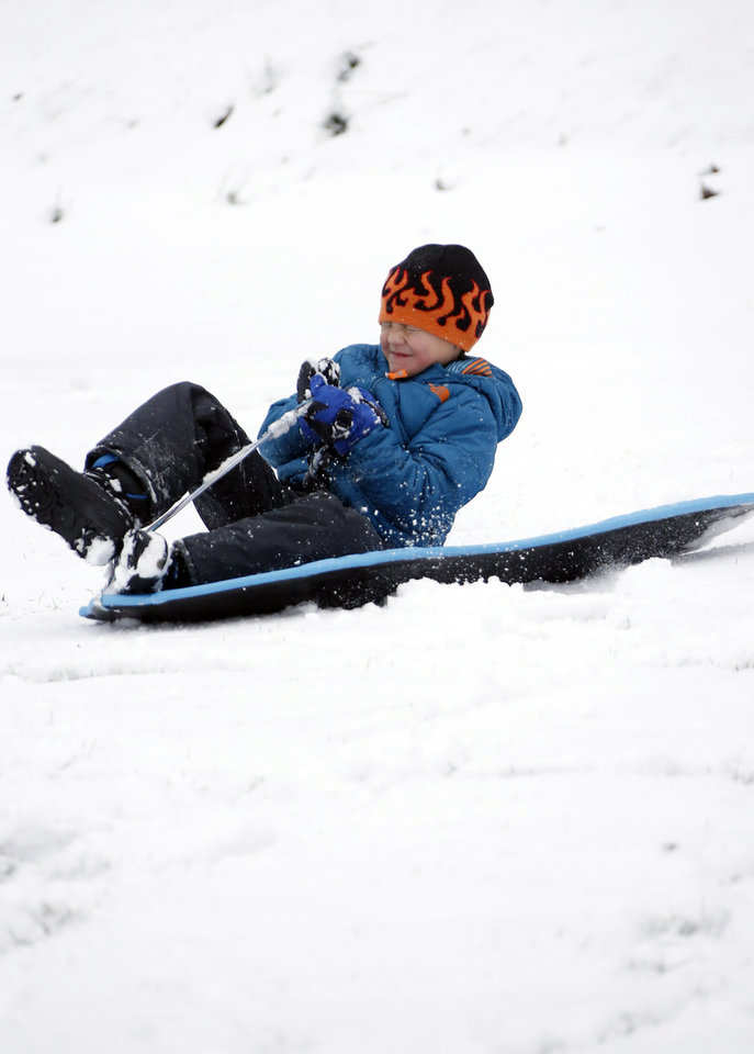 Photo - Guy Fruge, 7, enjoys sledding in the early Friday morning snow in Avent Park in Oxford, Miss., Jan. 22, 2016. Although the snow ceased falling, temperatures are expected to drop in the afternoon making for hazardous driving in north Mississippi. (AP Photo/Rogelio V. Solis)