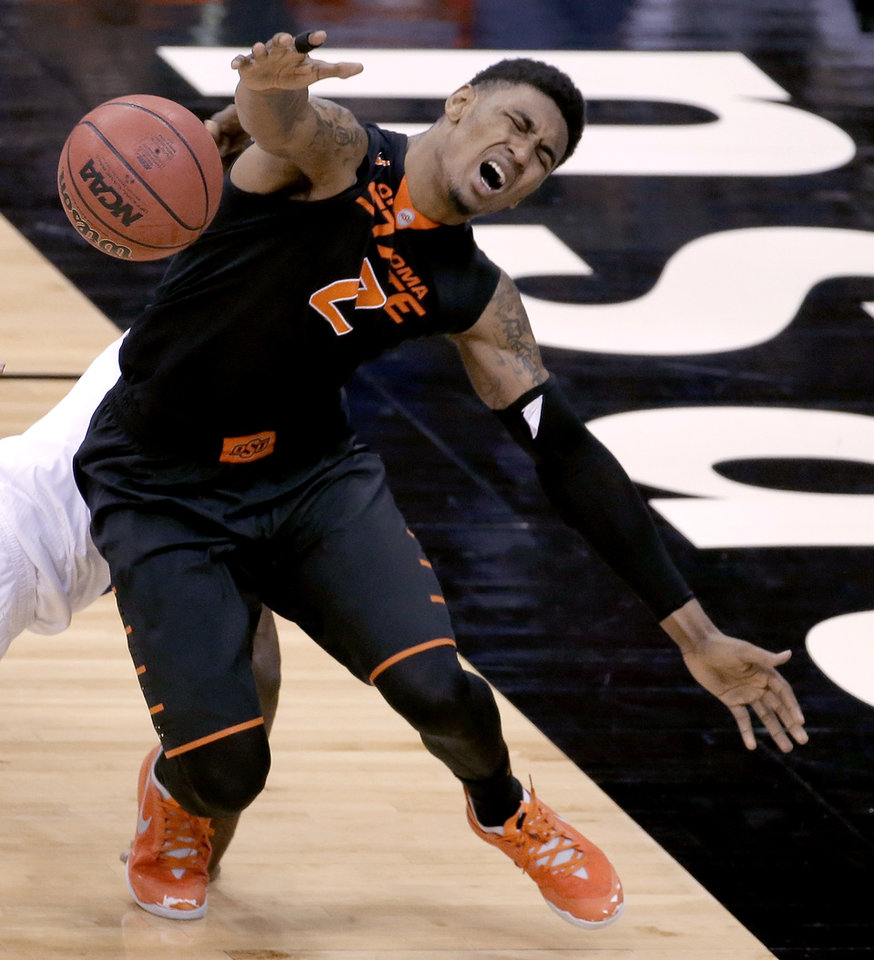 Photo - Oklahoma State's Le'Bryan Nash chases a loose ball during the second half of an NCAA college basketball game against Kansas in the Big 12 men's tournament Thursday, March 13, 2014, in Kansas City, Mo. (AP Photo/Charlie Riedel)