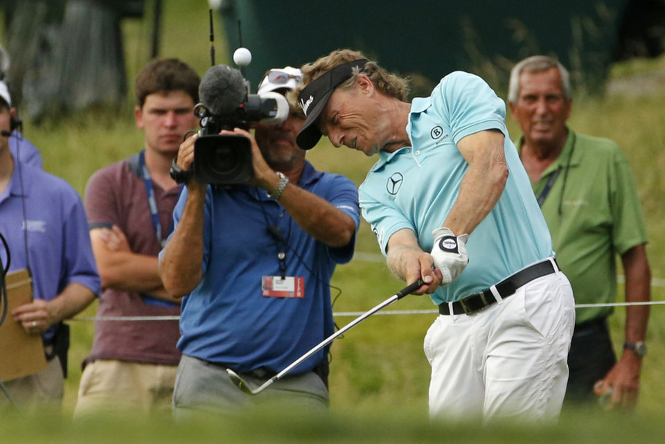 Photo - Bernhard Langer of Munich, Germany, hits out of the rough onto the 18th green, the second hole of a sudden-death playoff against Jeff Sluman during  the Senior Players Championship golf tournament at Fox Chapel Golf Club in Pittsburgh, Sunday, June 29, 2014. Langer sank a birdie putt and defeated Jeff Sluman on the second hole of the playoff to win the tournament. (AP Photo/Gene J. Puskar)
