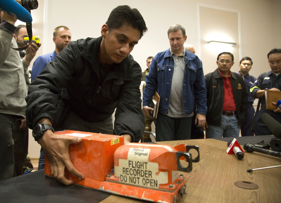 Photo - A Malaysian investigator takes a black box from Malaysia Airlines Flight 17 as it is handed over from Donetsk People's Republic officials to Malaysian representatives in the city of Donetsk, eastern Ukraine Tuesday, July 22, 2014. Bowing to international pressure Monday, pro-Moscow separatists released a train packed with bodies and handed over the black boxes from the downed Malaysia Airlines plane, four days after it plunged into rebel-held eastern Ukraine. (AP Photo/Dmitry Lovetsky)