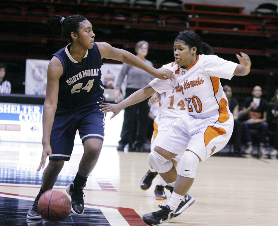 Photo - Booker T. Washington Hornets No.20 Rachel Block guards Southmoore Lady Sabercats No.24 Kyeria Hannah during the class 6A state tournament girls quarterfinal basketball game in Skiatook, Okla., taken on March 7,2013. JAMES GIBBARD/Tulsa World