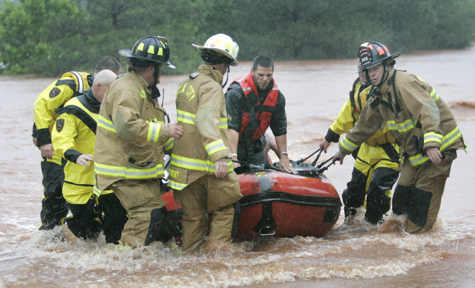 Photo - FLASH FLOODS / TORRENTIAL RAIN / FLOOD / FLOODING: Oklahoma City firefighters rescue two stranded motorists from a bridge near Hefner Road and Sooner Road in Oklahoma City, Oklahoma June 14 , 2010. Photo by Steve Gooch, The Oklahoman ORG XMIT: KOD