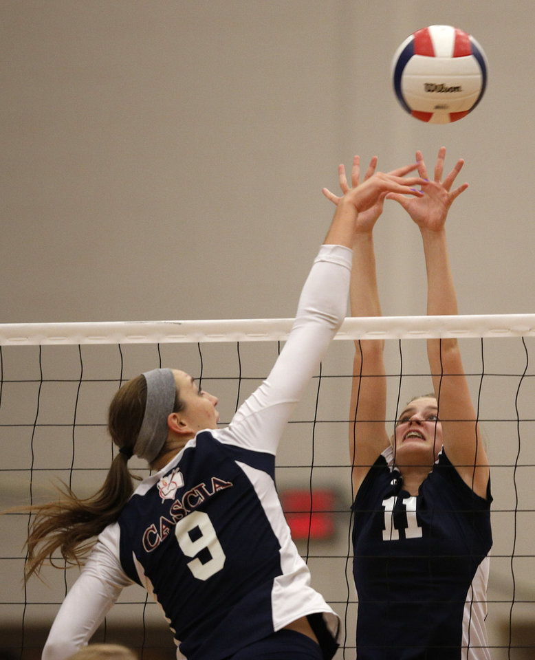Cascia Hall's Liesl Spoerl (9) spikes against Heritage Hall's Paige Miles (11) during the OSSAA 6A State Volleyball Championship between Bishop Kelley and Edmond Memorial at Westmoore High School in Moore, Okla., Saturday, Oct. 13, 2012.  Photo by Garett Fisbeck, The Oklahoman