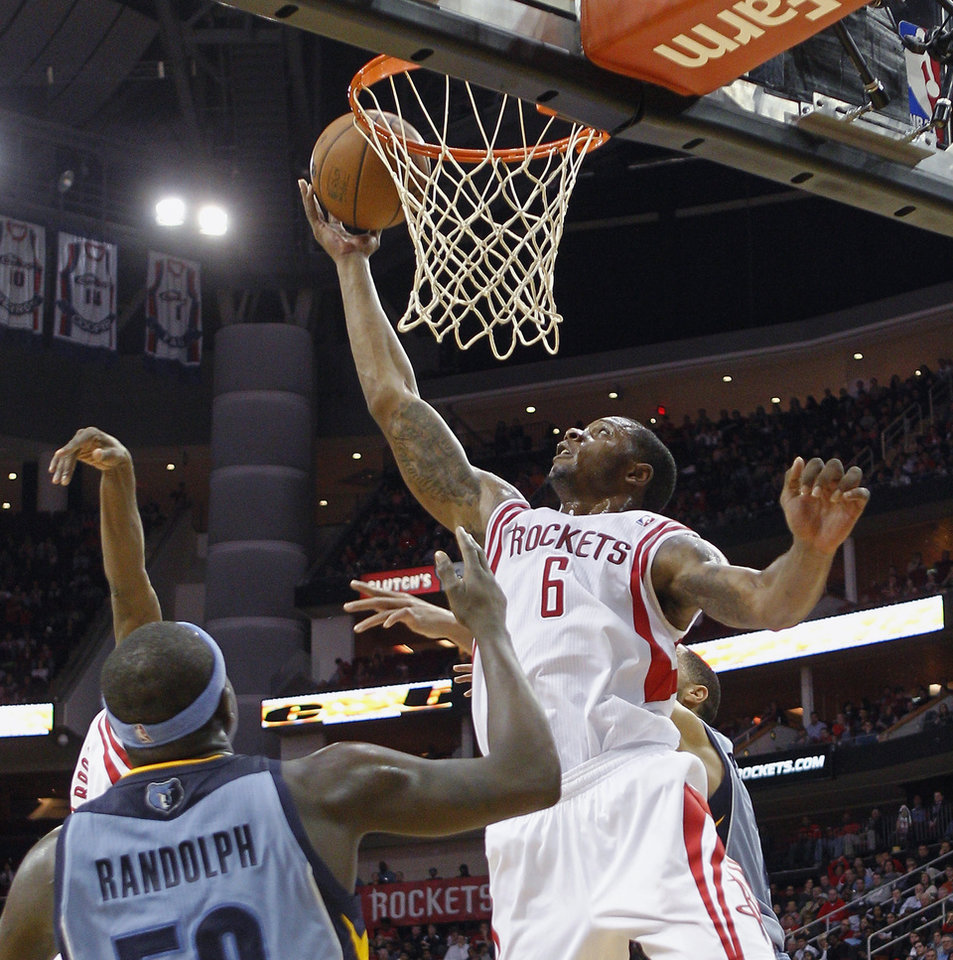 Photo - Houston Rockets forward Terrence Jones (6) tips in an offensive rebound as Memphis Grizzlies forward Zach Randolph (50) watches during the second half of an NBA basketball game Thursday, Dec. 26, 2013, in Houston. The Rockets won 100-92. (AP Photo/Bob Levey)