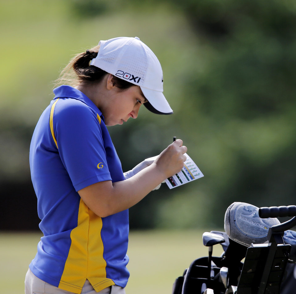 Photo - Mikera Morris of Dibble High School writes her strokes on a score card  during the 2014 Class 2A girls' golf state championship tournament  Wednesday, May 7, 2014, at Trosper Golf Course in Del City.  Photo by Jim Beckel, The Oklahoman