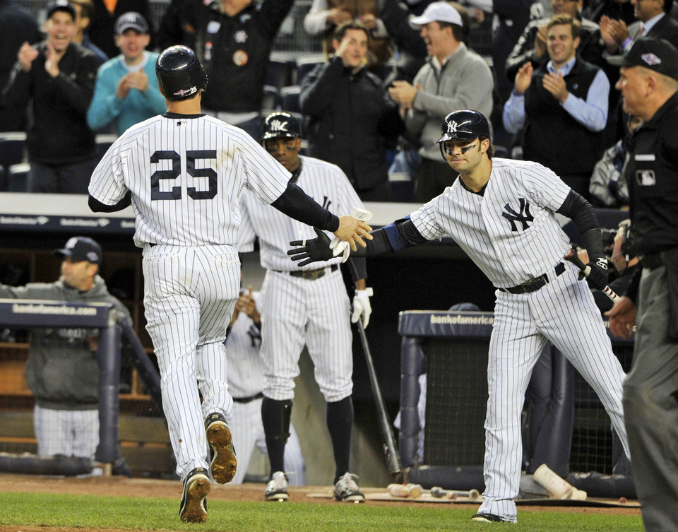 Photo -   New York Yankees' Mark Teixeira (25) is greeted by teammate Nick Swisher, right, after scoring on a hit by Raul Ibanez during the fifth inning of Game 5 of the American League division baseball series against the Baltimore Orioles, Friday, Oct. 12, 2012, in New York. (AP Photo/Bill Kostroun)